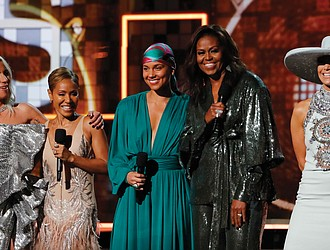 Former First Lady Michelle Obama, second from right, draws a standing ovation and cheers as she surprised the Grammy audience Sunday night to appear with, from left, Lady Gaga, Jada Pinkett Smith, host Alicia Keys and Jennifer Lopez.