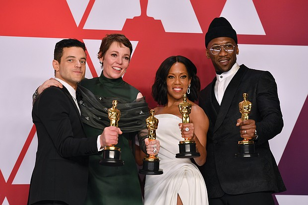 "Winners of the top acting awards pose for a photo in the press room following Sunday's awards show. They are, from left, Rami Malek, best actor in a leading role for ""Bohemian Rhapsody;"" Olivia Colman, best actress in a leading role for ""The Favourite;"" Regina King, best supporting actress for ""If Beale Street Could Talk;"" and Mahershala Ali, best supporting actor for ""Green Book."" Below, Hannah Beachler, left, and Jay Hart hold their Oscars high after winning the award for best production design for ""Black Panther."""