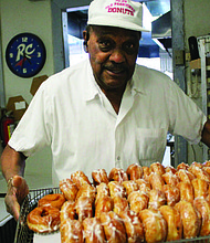 Buritt Bulloch, founder and owner of the Old Fashioned Donuts shop, shows off his famous glaze donuts he makes from scratch daily at his South Side restaurant. Photo by Wendell Hutson
