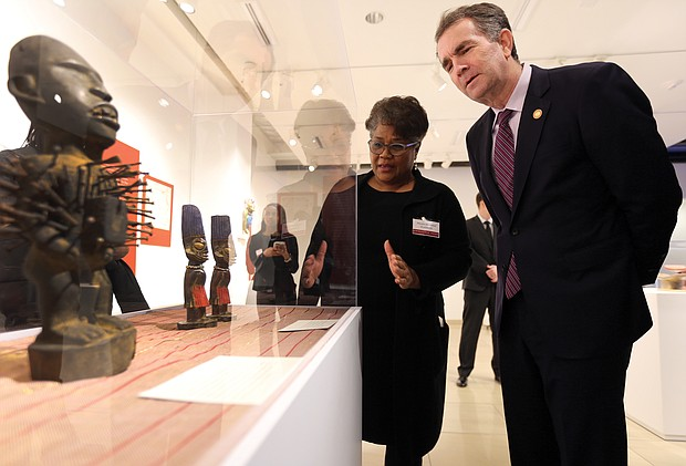 """'Unbound 2019: Truth & Reconciliation': In one of his first public appearances since the blackface scandal, Gov. Ralph S. Northam attends the opening of """"Unbound 2019: Truth & Reconciliation"""" on Feb. 28, at The Gallery at Main Street Station. This is the first part of a yearlong exhibition launched by the Richmond Slave Trail Commission to tell the stories of Africans in the Americas before 1619 through the present day. Mieko M. Timmons explains some of the exhibition pieces to Gov. Northam. Located on the first floor, the exhibition is open to the public without charge 8 a.m. to 5 p.m. daily at the station, 1500 E. Main St. Under Gov. McDonnell's administration, the state put up $11 million for various historical projects related to memorializing the enslaved in Virginia, including the Lumpkin's Jail site and a related museum in Shockoe Bottom and funds for the improvement of the Richmond Slave Trail. (Regina H. Boone/Richmond Free Press)"""