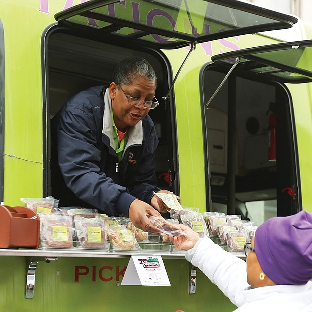 "'Mobile Soul Sunday'':Teresa Rogers leans out of the window of her food truck business, Sweet Temptations by Teresa, to sell a sweet treat to Evangeline Wood of Ashland on Sunday on Hull Street. Ms. Rogers' food truck was among 15 in South Side for ""Mobile Soul Sunday,"" the kickoff of the 2019 Richmond Black Restaurant Week Experience. The event, which runs through Sunday, March 10, highlights Richmond's black-owned restaurants, food truck and cart operators, caterers and local chefs. (Regina H. Boone/Richmond Free Press)"