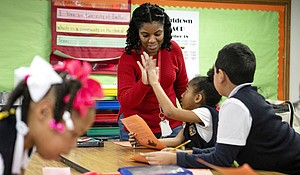 Natasha Boone high-fives a student while going over a story in class at Edward Titche Elementary School in Pleasant Grove. PHOTOGRAPHER: Leslie Boorhem-Stephenson CREDIT: The Texas Tribune