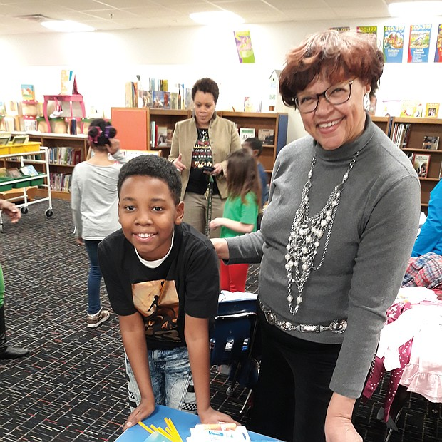 Giving to schools: Fifth-grader Kye'won Williams checks out some of the $1,000 in new school supplies Richmond City Councilwoman Ellen F. Robertson delivered last Thursday to his school, Overby-Sheppard Elementary in North Side, as Principal Kara Lancaster-Gay, in the background, talks with other students. (Jeremy M. Lazarus/Richmond Free Press)