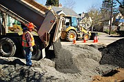 A city of Portland construction crew on Monday fills a whole left in the street caused by a broken water main, a major supply line that caused flooding, evacuations and a power outage of over 10,000 homes. Portland Water Bureau crew worked around the clock from when the pipe burst Saturday morning until a replacement was set and buried Monday morning.