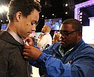 A Disney castmember teaches Disney Dreamer Brandon Griggs, 14, from Jacksonville, FL how to tie a tie