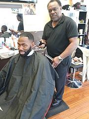 Mr. Barney cuts a customer's hair in his barbershop in Richmond.