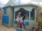 Youths celebrate a new home that Kenneth Barney and his Grace and Mercy Foundation built in Pignon, Haiti.