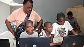Mr. Barney watches as Haitian youths use the laptops he took to Pignon.