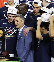Virginia head coach Tony Bennett, guard Ty Jerome (left) and their teammates celebrate after beating Texas Tech Monday for an  NCAA college basketball championship.  (AP photo)