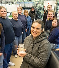 Oregon Zoo keeper Julia Low (foreground) shows a jar of tiny butterfly larvae to Coffee Creek inmates and correction officials during a tour of the zoo's butterfly lab last year.