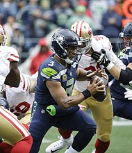 Seattle Seahawks Quarterback Russell Wilson scrambles in a NFL game against the San Francisco 49ers in 2017. The Oregon Lottery plans to bring back sports betting at the start of the new NFL season this fall, but has hit a stumbling block with its preferred contractor.  (AP photo)