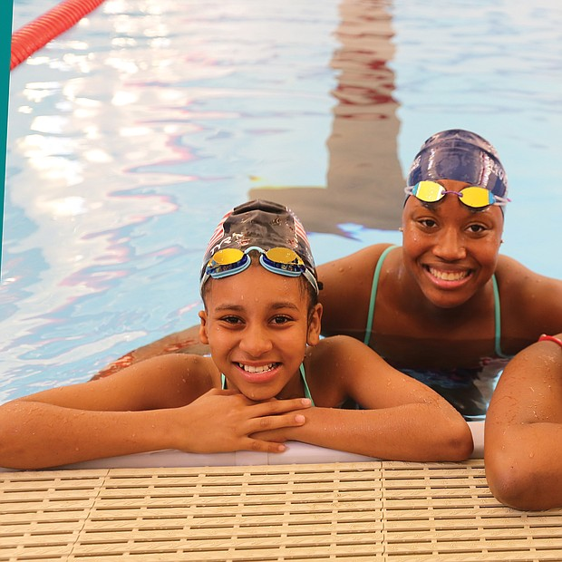Aquatic dreams: Cherish Daily, left, and T'Mya Harrison, right, sixth-grade and eighth-grade students, respectively, at Richmond's Franklin Military Academy, pose with Olympic medalist Simone Manuel Tuesday during Splash Day at the newly renovated pool at the Salvation Army Boys & Girls Club in the East End. (Regina H. Boone/Richmond Free Press)