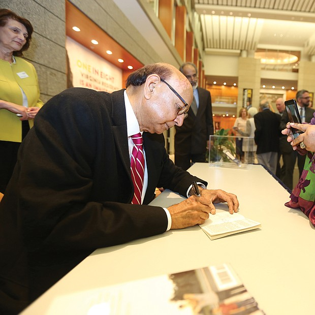 "An American story: Khizr Khan of Charlottesville, the father of a U.S. Army captain killed in Iraq in 2004, talked about his new book, ""An American Family: A Memoir of Hope and Sacrifice. He appeared April 4 at the Library of Virginia in Downtown as part of the 2019 Carole Weinstein Author Series. He signs a copy of his book for Dr. Paige L. Chargois of Richmond. (Regina H. Boone/Richmond Free Press)"