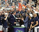 University of Virginia Cavaliers players celebrate their first NCAA Tournament championship win Monday night with Coach Tony Bennett, third from right, on the podium at U.S. Bank Stadium in Minneapolis. The team's 85-77 victory over Texas Tech came during overtime. It was the first overtime victory in the tournament since 2008 and the eighth in tournament history.