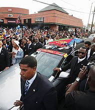 Following a memorial service that filled the Staples Center in Los Angeles Thursday for the late rapper Nipsey Hussle, thousands more people line Hussle's a 25-mile funeral procession through the streets of south Los Angeles.  (AP photo)