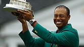Tiger Woods holds the championship trophy wearing the green jacket donned by winners after coming from behind to claim victory Sunday at the Masters Tournament in Augusta, Ga.