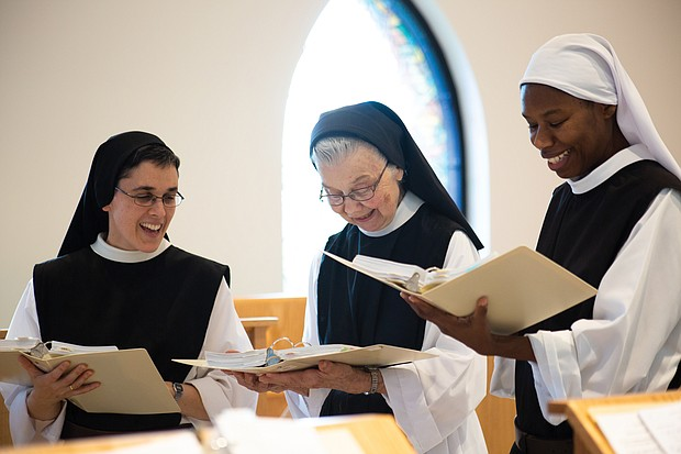 From left, Sister Maria Gonzalo, Sister Barbara Smickel and Sister Myriam Saint-Vilus take a break from cheese making to practice a song for Palm Sunday Mass.