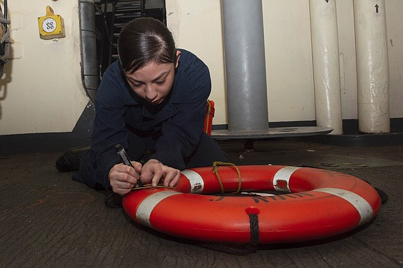 U.S. Navy Boatswain's Mate Seaman Kassandra Lopez, from Houston, stencils a life ring aboard the aircraft carrier USS John C. ...
