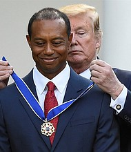 Tiger Woods being awarded by President Trump