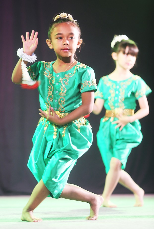Celebrating Asian-American culture: Gianna Sa, 7, of Chesterfield County, performs a traditional Cambodian dance with members of the Cambodian Dance Troupe of the Khmer Samacky Monastery in Henrico last Saturday during the 22nd Annual Asian American Celebration. (Regina H. Boone/Richmond Free Press)