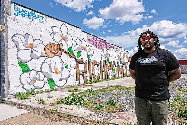 """T. """"Silly Genius"""" Sparks stands in front of the new mural that he and fellow muralist P.T. Carroll finished at 2604 Hull St., on the side of the Atlantis Food Service Equipment building. The two are among eight artists in the All City Art Club that began in 2017 to enliven neglected areas of the city.  """"Murals help make an area look better, then people feel better and then things will start to happen,"""" according to Silly Genius, who has led the club's efforts to secure commissions. (Sandra Sellars/Richmond Free Press)"""