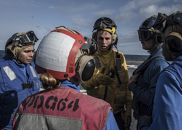 Boatswain's Mate Seaman Chance Vaughan, from Houston, Texas, gives a brief to the flight deck crew before flight operations aboard ...