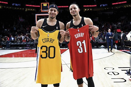 "Hold each others jerseys, Seth Curry of the Portland Trail Blazers (left) faces his brother Stephen ""Steph"" Curry of the Golden State Warriors in the NBA Western Conference Finals.  (AP photo)"