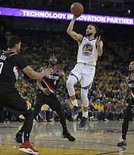 Golden State Warriors' Stephen Curry shoots between Portland Trail Blazers' Maurice Harkless (4), Enes Kanter and Damian Lillard (right) during Game 1 of the NBA basketball playoffs Western Conference finals Tuesdayin Oakland, Calif. (AP photo)