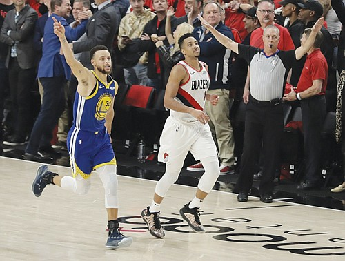 Golden State Warriors guard Stephen Curry celebrates as he runs next to Portland Trail Blazers guard CJ McCollum at the end of Game 4 of the NBA basketball playoffs Western Conference finals on Monday at the Moda Center. The Warriors won 119-117 in overtime.  (AP Photo/Ted S. Warren)