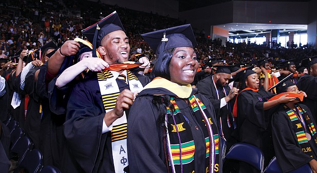 Adrien Passee places the commencement sash over the shoulders of fellow graduate Sara Parsons during the Sunday afternoon ceremony at the Virginia State University Multi-Purpose Center.