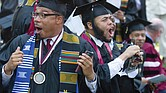 Shocked graduates, above, stand and cheer after commencement speaker billionaire technology investor and philanthropist Robert F. Smith, right, announces his family will provide a grant to eliminate the student debt of Morehouse College's entire 2019 graduating class, a gift valued at roughly $40 million.