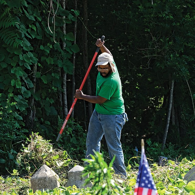 Celebrations of remembrance on Memorial Weekend/ Alan Delbridge, volunteer and outreach coordinator with Enrichmond Foundation, helps with cleanup efforts at the cemetery, the final resting place for many notable African-Americans including pioneering Richmond banker and businesswoman Maggie L. Walker. (Sandra Sellars/Richmond Free Press)