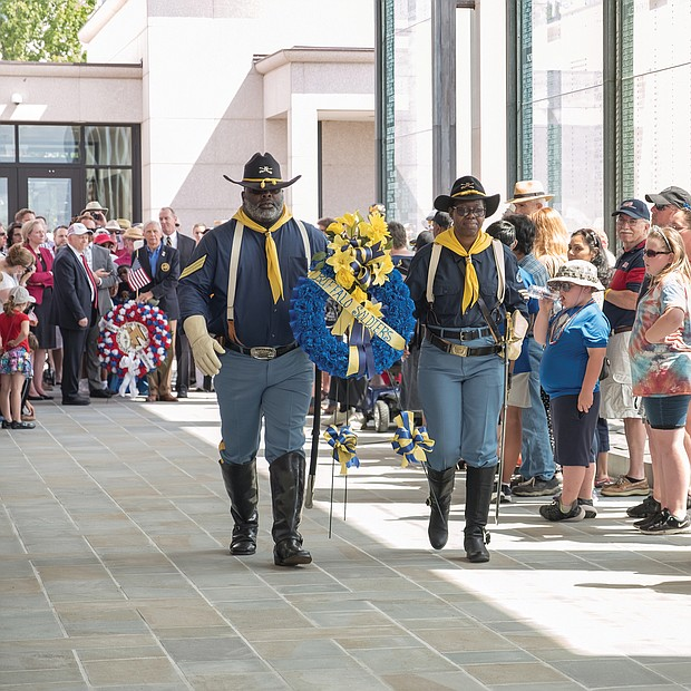 Celebrations of remembrance on Memorial Weekend/ Eddie Rose and Patricia Williams of the Mark Matthews Chapter of Petersburg, 9th and 10th Cavalry of the Buffalo Soldiers Association carry a wreath to be placed at the feet of the statue of Memory during Monday's 63rd Annual Commonwealth's Memorial Day Ceremony at the Virginia War Memorial on South Belvidere Street in Downtown. (Ava Reaves/Richmond Free Press)