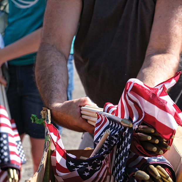 Celebrations of remembrance on Memorial Weekend/ On Saturday, John Harris distributes American flags, above right, to volunteers who placed them beside the graves of veterans buried at historic Evergreen Cemetery in the East End. (Sandra Sellars/Richmond Free Press)