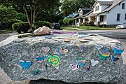 Messages of condolence and love, a tube of bubbles and flowers adorn a boulder at the entrance to Carter Jones Park on Wednesday.