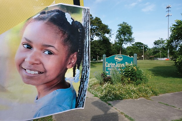 A flier bearing 9-year-old Markiya Dickson's picture is posted near an entrance to Carter Jones Park at 28th and Perry streets in South Side. The Chesterfield County third-grader was shot and killed at the park on Sunday. An 11-year-old was wounded.