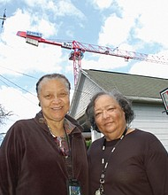 Mary Batson (left) and her sister, Virgie Ruiz, became concerned about a transformer-mounted pole installed in front of their house to accommodate new luxury apartments in their gentrifying neighborhood.  Now Portland Bureau of Transportation says the pole was improperly placed and may ask Pacific Power to move it.