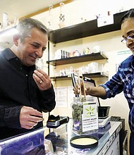 Adam Smith, founder and executive director of the Oregon Craft Cannabis Alliance is shown a marijuana variety by Tree PDX marijuana shop owner Brooke Smith at her shop in Portland. Smith is part of a newly formed group that will launch an ad campaign to support mom-and-pop cannabis retailers.