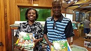 Juliana Ocansey and her father, John Ocansey, pose with some of the books they plan to send to a school in Accra, Ghana. Their hope is by getting the children reading early they will become educated and live better lives.  (Photo courtesy Will County Executive Larry Walsh's office)
