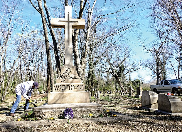 Volunteer Brenda Jones plants flowers at Maggie L. Walker's gravesite in this March 11, 2017, photo of work being done to restore and improve Evergreen Cemetery after decades of neglect.