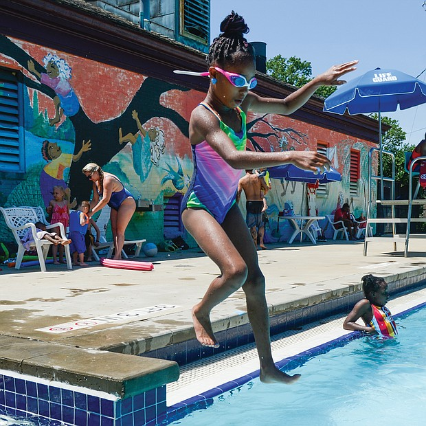 Pool's open! Gianni Harris, 7, jumps into the Battery Park pool Saturday to enjoy the cool water with family and friends. The joyful noise and splashes of youngsters marked the official opening last weekend of the City of Richmond's seven outdoor swimming pools. (Clement Britt/Richmond Free Press)