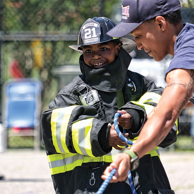 Learning the ropes/ Many youngsters dream of being firefighters when they grow up. Ralph Lee Harris III got to live out the dream during Richmond Fire Station 21's Community Day event last Saturday at the station, 2505 Jefferson Davis Highway. Dressed out, the youngster helps Firefighter Brianna Robinson of Engine Co. 11 during a hose drill. (Sandra Sellars/Richmond Free Press)