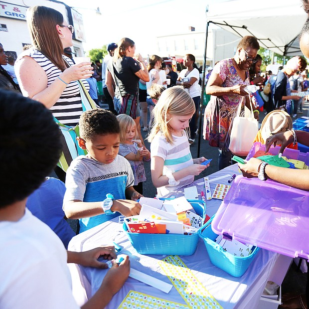 """'In The Sun Again' At the Robinson Theater Community Arts Center's """"In The Sun Again Community Block Party"""" last Friday at the Church Hill, Karen Wells, right, introduces children to art activities at the PBS """"Ready to Learn"""" table in her role as East End manager for the PBS program. The block party continues the theater's efforts to be a place that creates connections between residents and supports diversity and inclusion. (Regina H. Boone/Richmond Free Press)"""