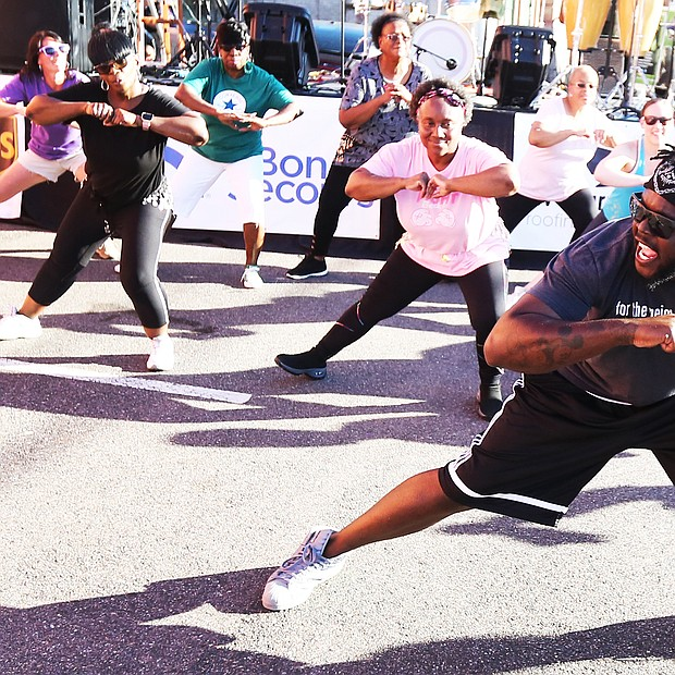 """'In the Sun Again'/ Me'Kel Williams leads a cardio hip-hop session during the Robinson Theater Community Arts Center's """"In The Sun Again Community Block Party"""" last Friday at the Church Hill center. Mr. Williams demonstrated the workout he leads weekly at the center, where he is assistant director.  The block party continues the theater's efforts to be a place that creates connections between residents and supports diversity and inclusion. (Regina H. Boone/Richmond Free Press)"""