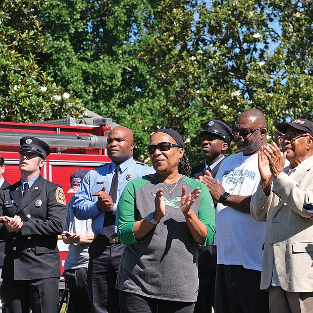 Honorary street sign for Fire Chief -Ronald C. Lewis Leslie A. Lewis, foreground, celebrates the unveiling and dedication of an honorary street sign honoring her late husband, former Richmond Fire Chief Ronald C. Lewis. Dozens of friends, neighbors, firefighters and supporters turned out for the sign's unveiling last Saturday at the intersection of Birdwood and Bathgate roads in South Side's Brookbury neighborhood, where the Lewis family lives. The trailblazing Chief Lewis was Richmond's first African-American fire chief, serving in the top position from 1978 to 1995. (Sandra Sellars/Richmond Free Press)