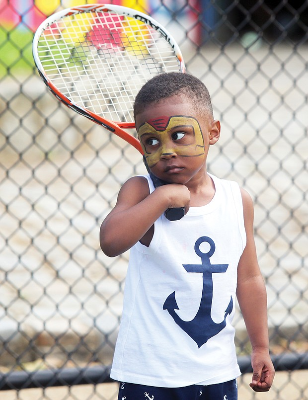 New to the game/ Darien Threatts, 2, channels his inner Ashe during a tennis skills session for children last Saturday at Battery Park in North Side. Friends of Battery Park collaborated with several other groups to put on the celebration at the park's Arthur Ashe Tennis Courts. (Regina H. Boone/Richmond Free Press)