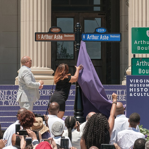Richmond City Councilwoman Kim B. Gray, 2nd District, pulls down the last curtain to unveil the new Arthur Ashe Boulevard signs as Mr. Ashe's nephew, David O. Harris Jr., left, and Mayor Levar M. Stoney watch.  (Ava Reaves/Richmond Free Press)