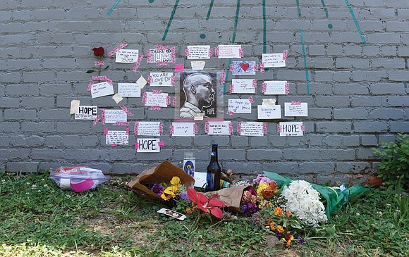 Tribute messages are posted on a side wall of Jade Multicultural Salon in Church Hill in remembrance of talented Richmond ...