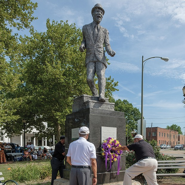 """From left, Jonathan Johnson, Eugene Harden and Edward Hamlin, past presidents of the Astoria Beneficial Club, place a wreath at the statue of Bill """"Bojangles"""" Robinson in Jackson Ward last Saturday during the organization's 46th annual commemoration of the Richmond native and entertainer. In 1933, Mr. Robinson used his own money to purchase a traffic light for the intersection of Leigh and Adams streets after witnessing the dangers young African-Americans faced in trying to cross the busy street. The Astorians placed the statue in his honor at the intersection 46 years ago. (Ava Reaves)"""