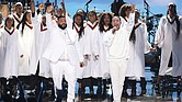 DJ Khaled and John Legend stand in front of a choir to lead a musical tribute to Nipsey Hussle during the BET Awards on June 23 at Microsoft Theater in Los Angeles.